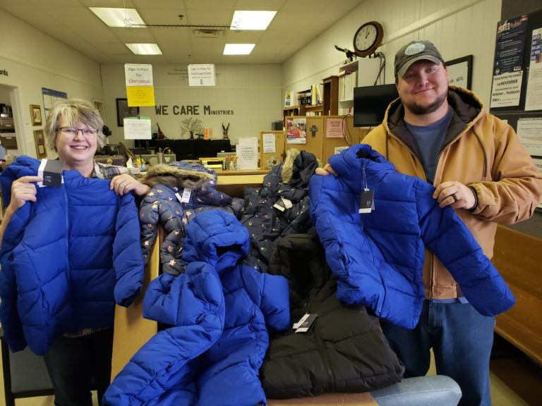 Charlie from Tennessee Inspection Services holds one of many coats being donated.